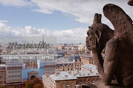 A gargoyle stares out from Notre Dame de Paris cathedral, Paris, France, Europe