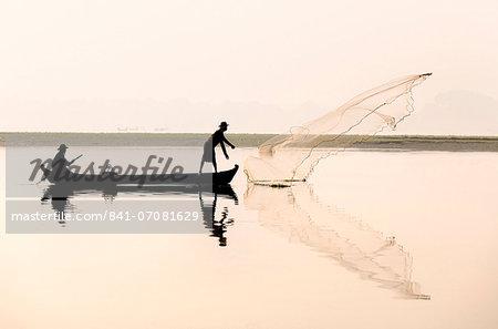 Fishermen on Taungthaman Lake in dawn mist, casting net near U Bein Bridge, Amarapura, near Mandalay, Myanmar (Burma), Asia