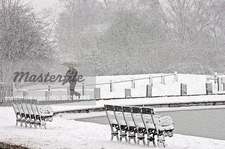 Man walks with umbrella across snow-covered Hampstead Heath, North London, United Kingdom