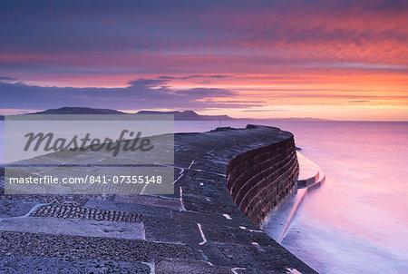 Sunrise in winter over the Jurassic Coast, UNESCO World Heritage Site, from The Cobb, Lyme Regis, Dorset, England, United Kingdom, Europe