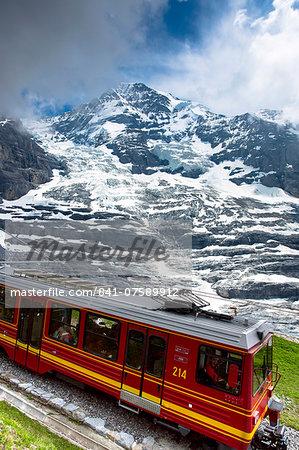 Jungfraubahn funicular train with Eiger Glacier (Eigergletscher) behind in Swiss Alps, Bernese Oberland, Switzerland, Europe