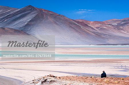 Man sitting on rocks at Miscanti Volcano and high plateau lagoon in San Pedro de Atacama desert, Chile, South America