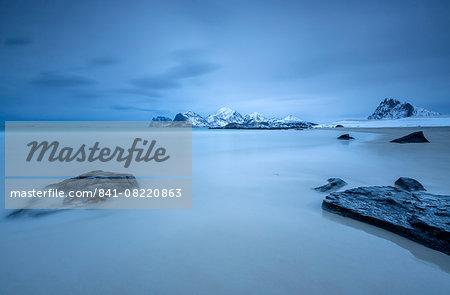 The cold blue sea bathes the beach still partially snowy. Myrland, Lofoten Islands, Northern Norway, Scandinavia, Arctic, Europe