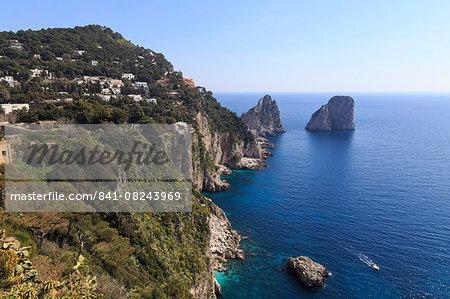View to limestone pinnacles of Faraglioni rocks from Giardini di Augusto, with spring flowers and boat, Capri Town, Capri, Italy, Mediterranean, Europe