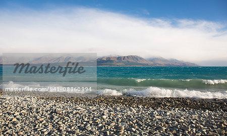 View from rocky shoreline across the stormy waters of Lake Pukaki, near Twizel, Mackenzie district, Canterbury, South Island, New Zealand, Pacific
