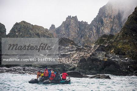 Tourists on a zodiac watching a dolphin colony, Elephant Island, South Shetland Islands, Antarctica, Polar Regions