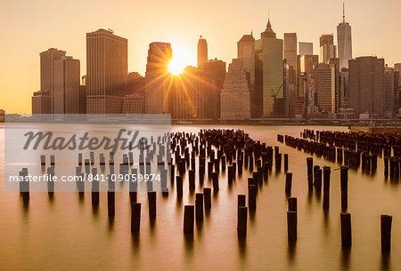 Lower Manhattan skyline, New York skyline, exposed wooden pier stumps, at sunset, East River, New York, United States of America, North America