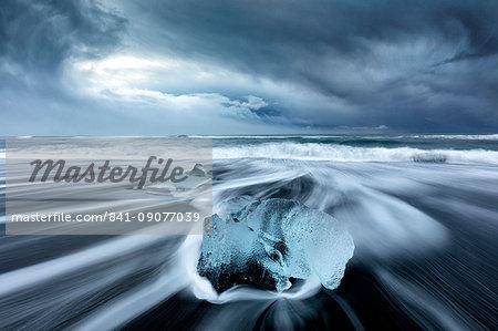 Glacier ice on black sand beach with waves washing up the beach on a stormy winter day, near Jokulsarlon, South Iceland, Polar Regions