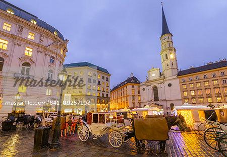 Christmas Market stalls and St. Michael Catholic Church in Michaelerplatz, Vienna, Austria, Europe