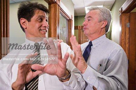 Two Multi-ethnic businessmen having discussion in office corridor