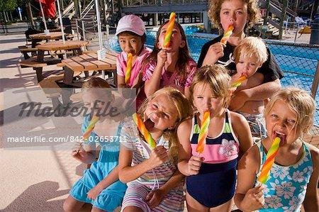 Group of children enjoying popsicles at water park