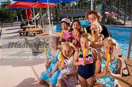 Children eating lollipop in water park