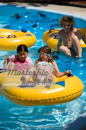 Children having fun at water park floating on innertubes