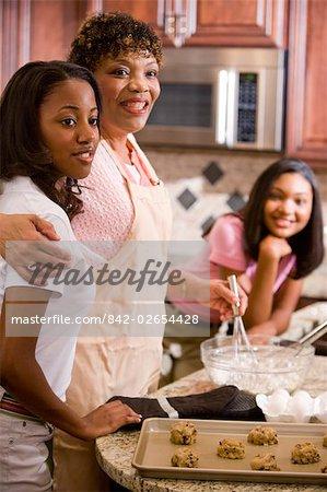 Portrait of parents/grandparents and teenage daughters baking cookies