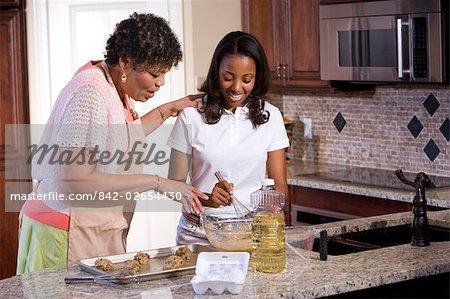 Portrait of mother/grandmother and teenage daughter baking cookies