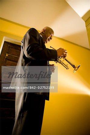 Senior African American musician holding trumpet in hallway