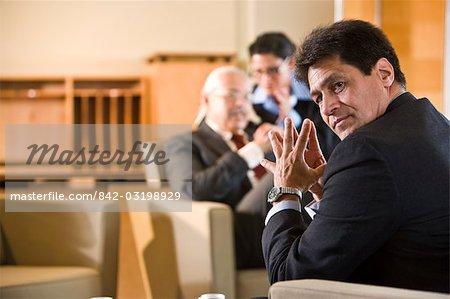 Hispanic businesspeople in serious meeting