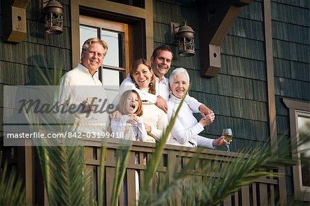 Happy multi-generational family standing on balcony