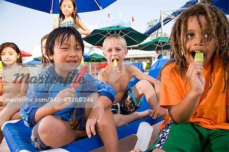 Multi-ethnic group of children eating popsicles