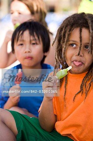 Multi-ethnic children eating popsicles at water park