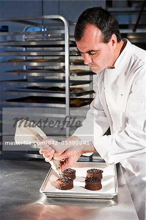 Pastry chef decorating chocolate dessert pastries