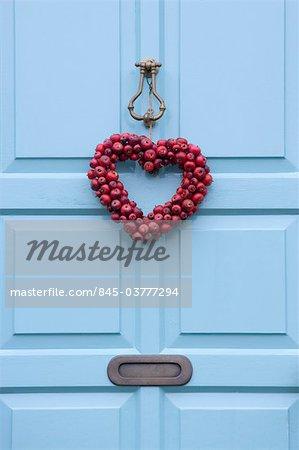 Christmas wreath on a sky blue door, England.