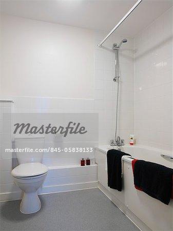 White tiled bathroom in new build social housing, East Thames Housing Group, John Street, Plaistow, London, UK. Architects: Greenhill Jenner Partnership
