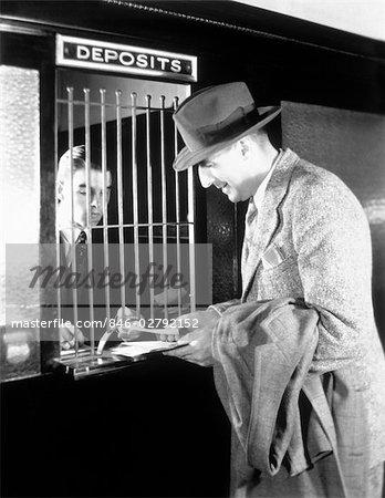1940s MAN AT TELLERS WINDOW OF BANK MAKING A DEPOSIT OR WITHDRAWAL