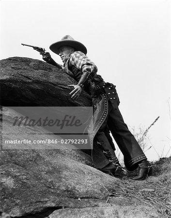 1930s COWBOY ON ROCKS AIMING GUN