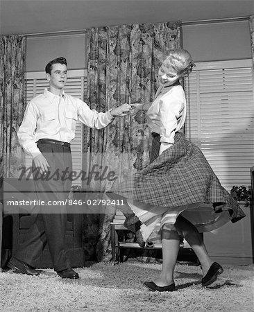 1950s TEEN COUPLE DOING THE JITTERBUG IN LIVING-ROOM