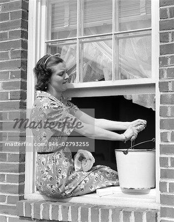 1930s WOMAN SITTING BACKWARDS ON WINDOW LEDGE WASHING WINDOW PANES