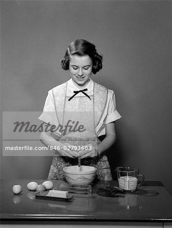 1950s YOUNG TEENAGE GIRL WEARING APRON BRAKING EGG INTO MIXING BOWL COOKING BAKING
