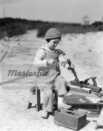 1920s BOY CAP OVERALLS USING HAMMER CHISEL WORKING WITH WOOD CARPENTER CARPENTERS TOOLS REPAIR REPAIRING BUILD