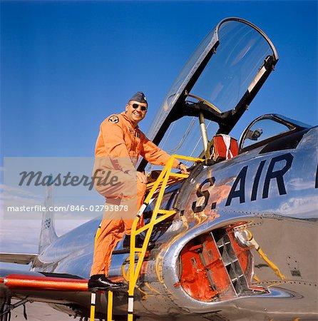 1970s SMILING MILITARY PILOT LADDER CLIMBING ENTER COCKPIT JET WEARING ORANGE FLIGHT JUMP SUIT PILOTS MEN