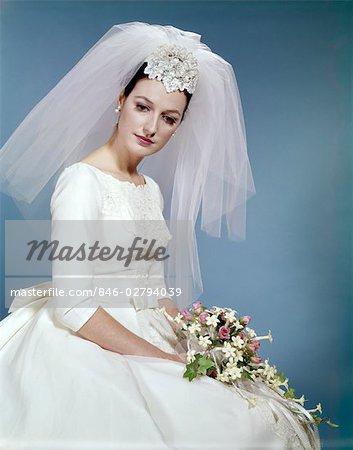 1960s FORMAL PORTRAIT OF BRIDE SITTING HOLDING FLOWER BOUQUET