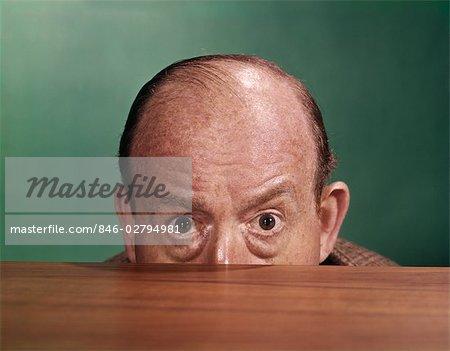 1960s BALDING MAN PEEKING OVER DESKTOP WITH ONLY TOP HALF OF HEAD SHOWING