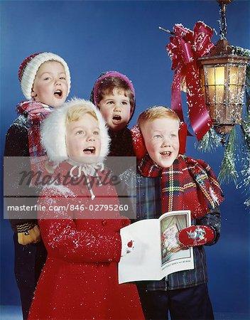 1960s CHILDREN BOYS GIRLS SINGING CHRISTMAS CAROLS UNDER HOLIDAY LANTERN