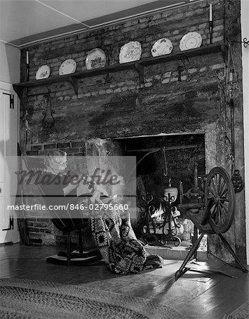 1950s ELDERLY WOMAN IN ROCKER IN FRONT OF FIREPLACE DOING NEEDLEWORK
