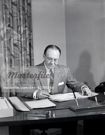 1950s MIDDLE AGED BUSINESSMAN EXECUTIVE SITTING DESK SIGNING PAPERS PENCIL PEN LIT CIGARETTE OFFICE BOSS WEAR SUIT TIE GLASSES