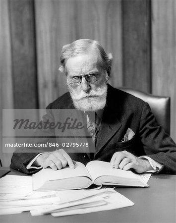 1930s ELDER MAN IN GLASSES SITTING AT DESK READING BOOK