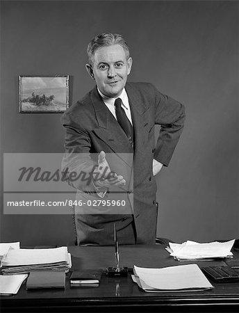 1950s MAN SMILING BUSINESSMAN SALESMAN REACHING ACROSS DESK TO SHAKE HANDS