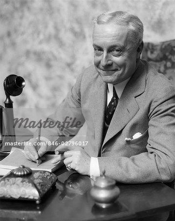 1920s 1930s SMILING MAN BUSINESSMAN SALESMAN SITTING AT DESK SMOKING CIGAR WRITING A MEMO