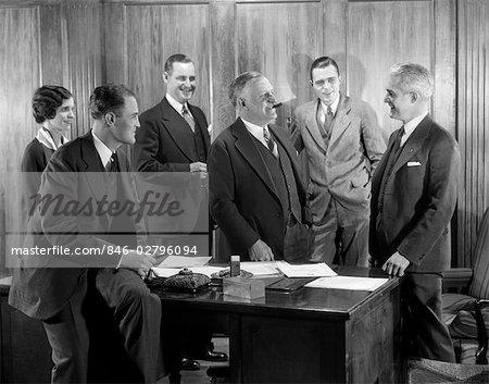 1930s SMILING OFFICE GROUP FOUR MEN ONE WOMAN BOSS SMOKING CIGAR TALKING MEETING FIFTH MAN