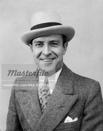 1930s HEAD & SHOULDER PORTRAIT OF SMILING MAN IN HERRINGBONE SUIT PAISLEY TIE & WHITE HAT