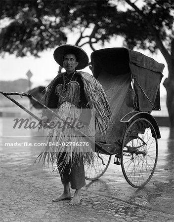 1930s RICKSHAW RIKSHA JINRIKSHA COOLIE IN RAIN COAT MADE OF GRASS STRAW TAXI TRANSPORTATION WORKER HONG KONG CHINA