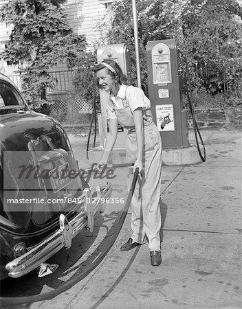 1940s woman gas station attendant filling car tank stock photo