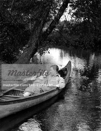 1930s SMILING COUPLE RECLINING CANOE BANK STREAM WOMAN DRESS THE MAN SPORT SHIRT JODHPURS GRASS TREES WATER