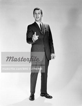 1960s MAN FULL LENGTH PORTRAIT POINTING GESTURE WEARING SUIT BUSINESSMAN SPOKESPERSON