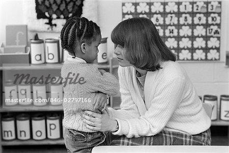 1980s GRADE SCHOOL TEACHER BENDING DOWN TO COMFORT ANGRY UPSET AFRICAN AMERICAN FEMALE STUDENT