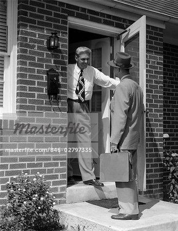 1950s Salesman Talking To Man At Front Door Stock Photo
